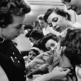 Woman Piercing Another Woman's Ears as Friends Look On Photographic Print by Robert W. Kelley