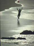 Young Woman in Silhouette Running Along Beach at Twilight Throwing Beach Ball Up in the Air Premium Photographic Print by Co Rentmeester