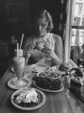 Teenaged Girl Sitting in Drugstore Eating a Hamburger Photographic Print by Hank Walker