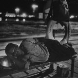 Weary Workman Resting Head on Steel Helmet While Lying on Bench Photographic Print by Cornell Capa