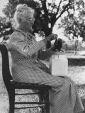 Old Woman in Gingham Dress Using Small, Modern Churn with Jar Sitting on Her Lap, on Farm Premium Photographic Print by George W. Ackerman