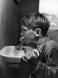 Young Boy Drinking from a Water Fountain Premium Photographic Print by Allan Grant