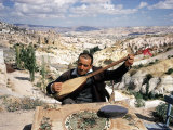 Turkish Man Playing a Type of Mandolin Called a Sis Reproduction photographique sur papier de qualité par Bill Ray