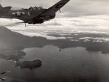 Navy Warplane Soaring over Tanahmerah Bay as Landing Craft Streaks For Beach Far Below Premium Photographic Print