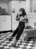 Young Girl Wearing Cowgirl Outfit Drinking Milk and Eating Sandwich in Kitchen Reproduction photographique par Nina Leen