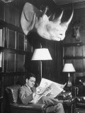 Member Reading Newspaper in Smoking Room at the Harvard Club Beneath a Rhino Head Trophy Photographic Print by Alfred Eisenstaedt