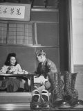 US Soldier and Local Girl Sharing a Meal in Local Establishment, with Shoes Sitting by Door Premium Photographic Print by John Florea