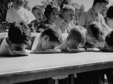 Pie Eating Contest During Church Social Premium Photographic Print by Al Fenn