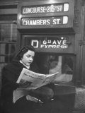 "Young Woman Wearing a Winter Coat and Hat, Reading Beneath ""D 6th Avenue"" Sign, Riding the Subway Photographie par Eliot Elisofon"