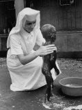 Sister Therese is Bathing a Child Suffering from Protein Deficiency Disease Premium Photographic Print by Terence Spencer