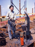 War Worker Holding Red Hot Metal Piece with Tongs at Shipyard Photographic Print by George Strock