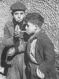 Two Homeless Boys Lighting Up American Cigarettes with British Matches Premium Photographic Print by George Rodger