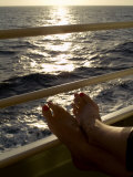 Woman's Feet Resting on the Railing of a Cruise Ship at Sunset Photographic Print by Todd Gipstein