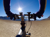 A Man Cycling Across a Desert Landscape Photographie par Barry Tessman
