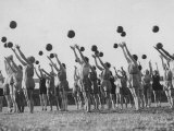 Women's Gym Class with Rows of Women Throwing Balls Into Air in Unison Photographic Print