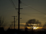 Row of Telephone Poles with Jet Contrails and Sunset in the Distance Photographic Print by Todd Gipstein