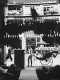 Young Man Standing in Front of a Herbs and Fish Market Displaying Racks of Fish Photographic Print by Howard Sochurek