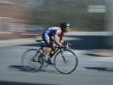 A Bicyclist Speeds Past in a Race Fotoprint van Heather Perry