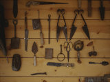 An Assortment of Hand Tools Hang on a Plank Wall Photographic Print by Raul Touzon
