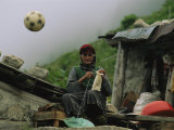 A Soccer Ball Flies over the Head of Woman Who is Knitting Outdoors Photographic Print by Randy Olson