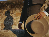 A Man in Traditional Dress Casts a Shadow against a Stone Wall Photographic Print by Raul Touzon