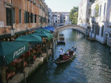 A Gondolier Passes a Restaurant on a Canal in Venice, Italy Photographic Print by Taylor S. Kennedy