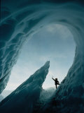A Climber Raises His Ax in Triumph Near the Opening of an Ice Cave Photographic Print by George F. Mobley