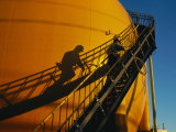 A Workman Climbs a Stairway on a Petroleum Storage Tank Photographie par Sisse Brimberg