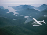 A Beaver Airplane on Floats Flies over Islands and Snowy Mountains Fotografisk tryk af Joel Sartore