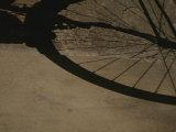 A Bicycle Wheel Casts a Shadow on a Wall and Sidewalk in Siena Impressão fotográfica por Raul Touzon