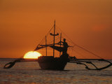 A Man and an Outrigger Silhouetted against a Brilliant Orange Sky Photographic Print by Paul Chesley