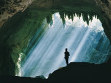 A Man Stands Below the Mouth of a Giant Cave Photographic Print by David Boyer