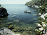 A Small Motorboat in a Lake Malawi Cove Photographie par Bill Curtsinger