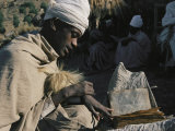 A Man in a Turban Sits Outside Reading Photographic Print by Michael S. Lewis