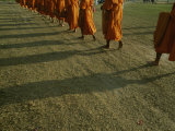 A Group of Buddhist Monks Walk Single-File Down a Dirt Road Photographic Print by Jodi Cobb