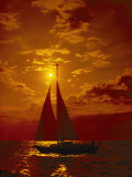 A Passing Sailboat is Silhouetted against a Brilliant Orange Sunset Near Bermuda Photographic Print by Todd Gipstein