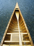 The Bow and Oar of a Handmade Wooden Canoe Resting in Water Photographie par Bill Curtsinger