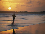 A Man Runs Through the Surf on Shella Beach at Sunset Photographic Print by Bobby Model