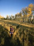 A Man Runs Through a Meadow of Tall Grass Near Mt. Elden Photographic Print by John Burcham