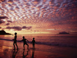Sunset Reddens a Cloudy Sky as Silhouetted Children Play on the Beach Photographic Print by Steve Raymer