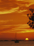 A Sailboat is Silhouetted by a Brilliant Orange Sunset Photographic Print by Nicole Duplaix
