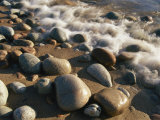 Water Washes up on Smooth Stones Lining a Beach Stampa fotografica di Michael S. Lewis