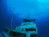 A Diver Exploring a Shipwreck with Fish Nearby Photographic Print by Nick Caloyianis