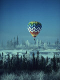 Hot Air Balloon Hovers Over a Snowy Landscape Photographic Print by George F. Herben