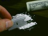 A Hand Dividing up a Pile of Cocaine with a Razor Blade Photographic Print by Todd Gipstein