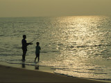 A Man and a Young Boy Fish in the Surf on an Assateague Beach Fotografie-Druck von Medford Taylor