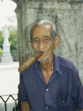 An Old Man Smokes an Over-Sized Cigar Fotografisk tryk af David Evans