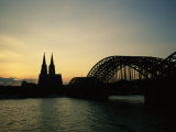 The Cologne Cathedral and Hohenzollern Bridge Silhouetted at Dusk Photographic Print by Raul Touzon