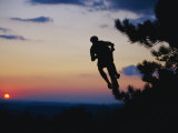 Silhouette of Mountain Biker in the Air against Sunset Sky Photographic Print by Skip Brown