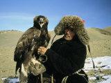 Un cazador de águilas posa con su águila en una llanura de Kazajistán Lámina fotográfica por George, Ed